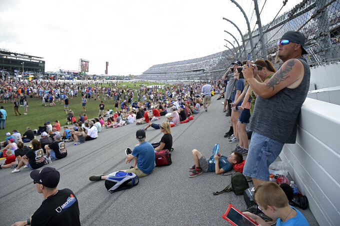 Spectators watch from the infield grass and track as entertainer Chris Lane performs before a NASCAR Cup Series auto race at Daytona International Speedway, Saturday, Aug. 28, 2021, in Daytona Beach, Fla. (AP Photo/Phelan M. Ebenhack)