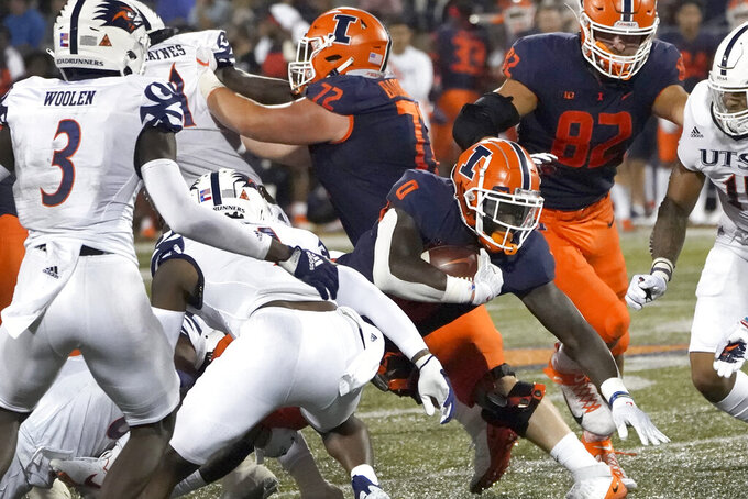 Illinois running back Joshua McCray (0) carries the ball through the UTSA defensive line during the first half of an NCAA college football game Saturday, Sept. 4, 2021, in Champaign, Ill. (AP Photo/Charles Rex Arbogast)