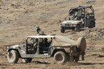 Israeli soldiers drive military vehicles during an exercise in the Israeli controlled Golan Heights near the border with Syria, Tuesday, Aug. 4, 2020. (AP Photo/Ariel Schalit)
