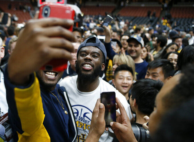 UC Irvine guard Max Hazzard, center, takes a selfie with a fan after an NCAA college basketball game against Cal State Fullerton for the Big West men's tournament championship in Anaheim, Calif., Saturday, March 16, 2019. UC Irvine won 92-64. (AP Photo/Alex Gallardo)