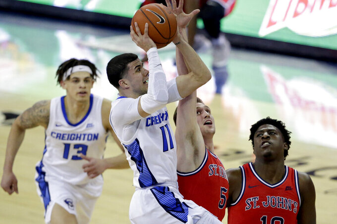 Creighton's Marcus Zegarowski (11) goes to the basket against St. John's David Caraher (5), with Jordan Scurry (12) and Marcellus Earlington (10) watching, during the first half of an NCAA college basketball game in Omaha, Neb., Saturday, Feb. 8, 2020. (AP Photo/Nati Harnik)