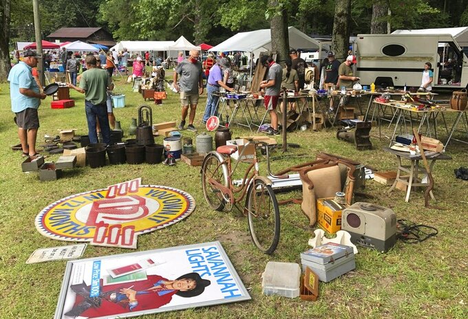 A crowd looks through items at the World's Longest Yard Sale, which stretches from Alabama to Michigan, at its southernmost point in Gadsden, Ala., on Thursday, Aug. 6, 2020. Promoters considered canceling the four-day sale because of the coronavirus pandemic but decided to go ahead with the event, now in its 34th year.   (AP Photo/Jay Reeves)