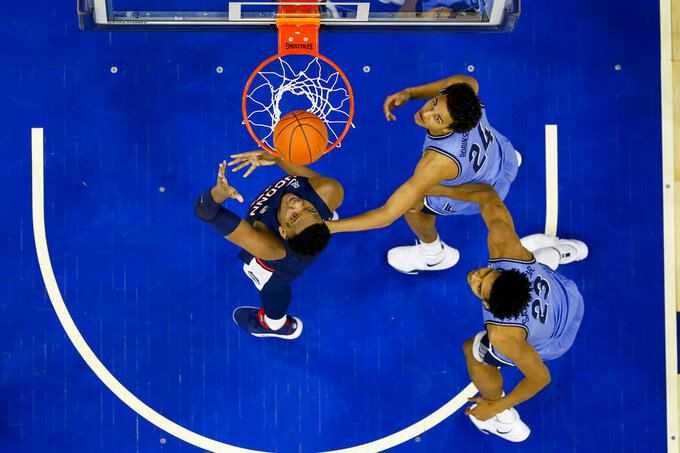 Connecticut's Josh Carlton, left, shoots the ball with Villanova's Jeremiah Robinson-Earl, center, and Jermaine Samuels, right, defending during the first half of an NCAA college basketball game Saturday, Jan. 18, 2020, in Philadelphia. (AP Photo/Chris Szagola)