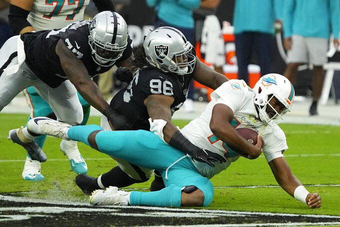 Las Vegas Raiders defensive tackle Darius Philon (96) tackles Miami Dolphins quarterback Jacoby Brissett (14) during the first half of an NFL football game, Sunday, Sept. 26, 2021, in Las Vegas. (AP Photo/Rick Scuteri)