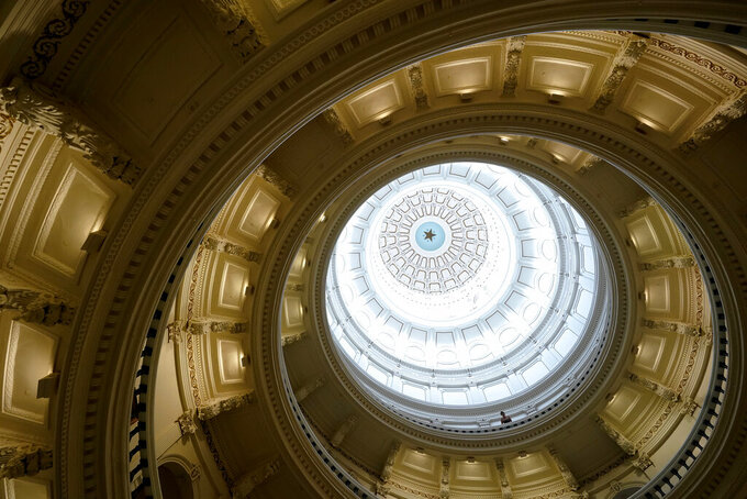 A visitor leans over a railing in the rotunda at the State Capitol, Tuesday, June 1, 2021, in Austin, Texas. The Texas Legislature closed out its regular session Monday, but are expected to return for a special session after Texas Democrats blocked one of the nation's most restrictive new voting laws with a walkout. (AP Photo/Eric Gay)