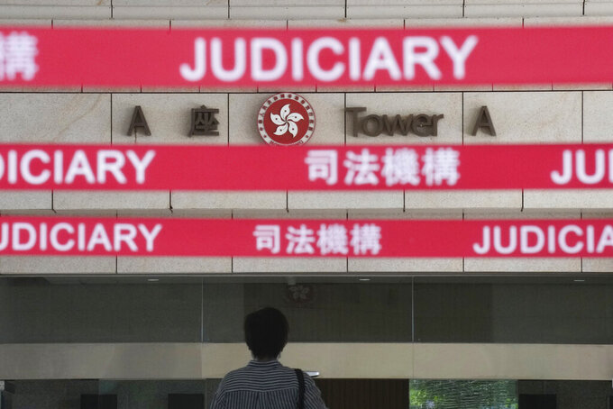 """A man walks toward the main entrance to local court in Hong Kong Thursday, July 22, 2021. Hong Kong police charged two top editors and two editorial writers at Apple Daily with collusion weeks after the city's largest pro-democracy newspaper was forced to cease publication and its assets were frozen. All four were charged with conspiring to """"collude with a foreign country or with external elements to endanger national security"""" under the city's year-old national security law and appeared in court Thursday. (AP Photo/Vincent Yu)"""