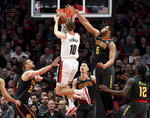 Portland Trail Blazers forward Jake Layman, center, drives to the basket between Atlanta Hawks center Alex Len, left, guard Jeremy Lin, center, forward Omari Spellman, center right, and forward Taurean Prince, right, during the first half of an NBA basketball game in Portland, Ore., Saturday, Jan. 26, 2019. (AP Photo/Steve Dykes)