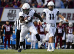 Connecticut running back Kevin Mensah (34) runs for yards as Connecticut quarterback Jack Zergiotis (11) looks from behind during the first half of an NCAA college football game against Massachusetts, Saturday, Oct. 26,, 2019, in Amherst, Mass. (AP Photo/Jessica Hill)