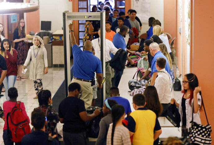 FILE - In this Sept. 6, 2016, file photo, students at William Hackett Middle School have their bags checked and pass through metal detectors on the first day of school in Albany, N.Y. Twenty years after the Columbine High School shooting made practicing for armed intruders as routine as fire drills, many parents have only tepid confidence in the ability of schools to stop a gunman, according to a new poll by The Associated Press-NORC Center for Public Affairs Research. (AP Photo/Mike Groll, File)