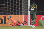 Portland Timbers goalkeeper Steve Clark, left, makes a save as defender Larrys Mabiala (33) stands nearby during the first half of an MLS soccer match against the LA Galaxy, Monday, July 13, 2020, in Kissimmee, Fla. (AP Photo/Phelan M. Ebenhack)