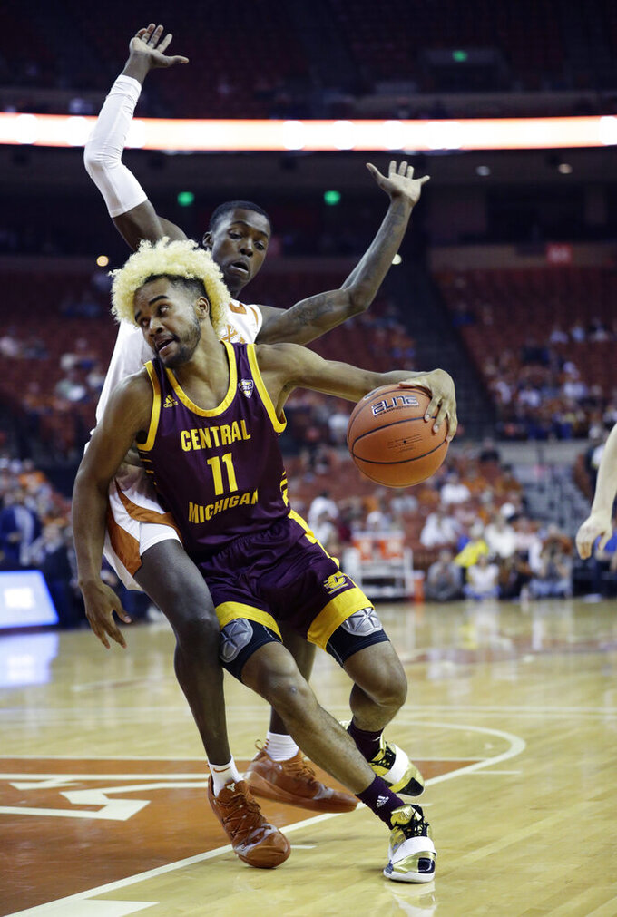 Central Michigan guard Deschon Winston (11) drives around Texas guard Andrew Jones (1) during the first half of an NCAA college basketball game, Saturday, Dec. 14, 2019, in Austin, Texas. (AP Photo/Eric Gay)