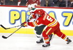 Minnesota Wild defenseman Matt Dumba (24) is tied up by Calgary Flames defenseman Mark Giordano (5) during the second period of an NHL hockey game Thursday, Jan. 9, 2020, in Calgary, Alberta. (Larry MacDougal/The Canadian Press via AP)
