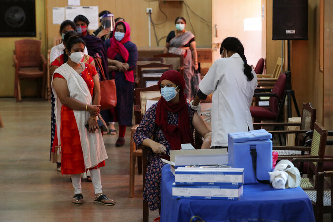 An Indian woman is administered a dose of Covishield, Serum Institute of India's version of the AstraZeneca vaccine as others wait their turn in Bengaluru, India, Wednesday, May 19, 2021. India has the second-highest coronavirus caseload after the U.S. with more than 25 million confirmed infections. (AP Photo/Aijaz Rahi)