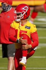 Kansas City Chiefs quarterback Patrick Mahomes stretches during an NFL football training camp Saturday, Aug. 22, 2020, at Arrowhead Stadium in Kansas City, Mo. The Chiefs opened the stadium to 2,000 season ticket holders to watch practice as the team plans to open the regular season with a reduced capacity of approximately 22 percent or normal. (AP Photo/Charlie Riedel)