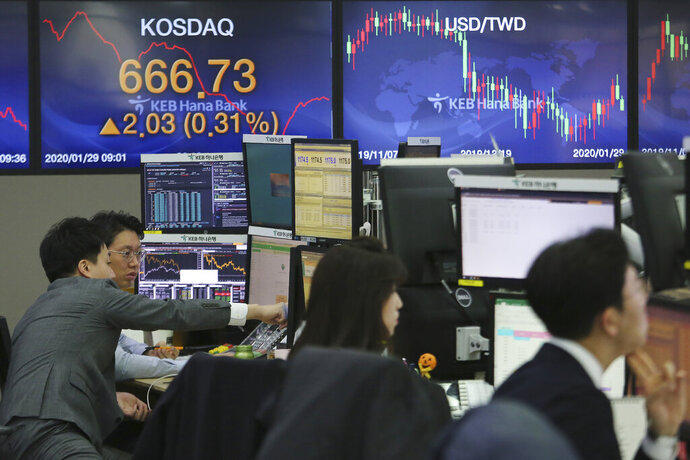 Currency traders watch monitors at the foreign exchange dealing room of the KEB Hana Bank headquarters in Seoul, South Korea, Wednesday, Jan. 29, 2020. Shares are mostly higher in Asia after a rebound on Wall Street that reversed most losses from a sell-off the day before. (AP Photo/Ahn Young-joon)