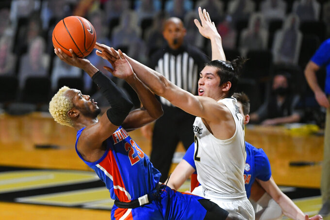 Florida guard Scottie Lewis shoots as Vanderbilt forward Quentin Millora-Brown, right, defends during the second half of an NCAA college basketball game Wednesday, Dec. 30, 2020, in Nashville, Tenn. Florida won 91-72. (AP Photo/John Amis)