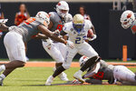 Tulsa running back Anthony Watkins (23) is defended by Oklahoma State defensive end Tyler Lacy (89) in the first half of an NCAA college football game, Saturday, Sept. 11, 2021, in Stillwater, Okla. (AP Photo/Sue Ogrocki)