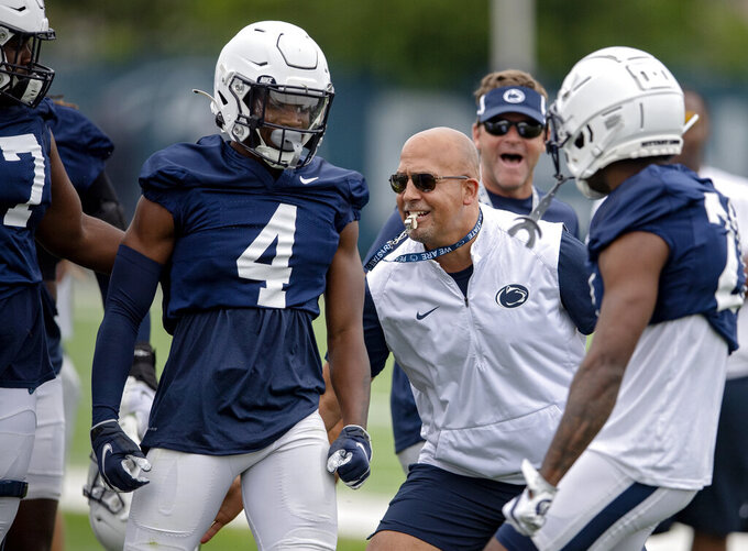 FILE - Penn State football coach James Franklin, second from front right, congratulates freshman cornerback Kalen King (4) after winning a 1-on-1 against a wide receiver during an NCAA college football practice  in State College, Pa., in this Saturday, Aug. 7, 2021, file photo. Penn State coach James Franklin believes new play-caller Mike Yurcich will help the Nittany Lions return to their 2016-2019 form where they scored 30 or more in 35 of 53 games and never averaged less than 34 points per game. (Abby Drey/Centre Daily Times via AP)