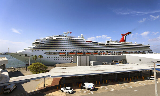 """FILE - In this Wednesday, May 12, 2021, file photo, the Carnival Cruise ship """"Liberty"""" is docked at Port Canaveral, Fla.  Carnival Corp. continues to lose billions while it waits for cruising to recover from the pandemic. Carnival said Thursday, June 24,  that it lost $2.1 billion in its latest quarter.   (Joe Burbank/Orlando Sentinel via AP)"""