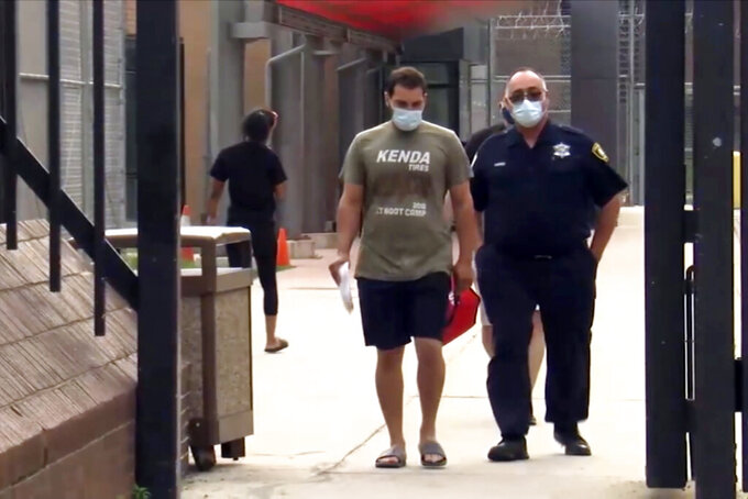 """FILE - In this July 8 2021, file image taken from video provided from ABC7, Keegan Casteel leaves jail at the 18th District police headquarters in Chicago. Casteel, an Iowa man arrested by Chicago police for having guns and ammunition in his hotel room overlooking a Lake Michigan beach, told responding officers he """"didn't mean to startle anyone"""" and simply forgot to remove the firearms from a bag while packing for a trip to the city. (ABC7 via AP, File)"""