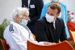 French President Emmanuel Macron, right, talks to a resident at the 'La Bonne Eure' nursing home in Bracieux, central France, Tuesday, Sept. 22, 2020. For the first time in months, virus infections and deaths in French nursing homes are on the rise again. (Yoan Valat/Pool Photo via AP)
