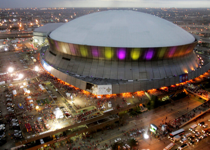 FILE - In this Jan. 7, 2008, file photo, color lights play on the Louisiana Superdome at twilight before the BCS championship college football game in New Orleans.  The home to the Saints football team, will get $450 million in renovations if Louisiana officials agree to the financing plans. Upgrades to the iconic, 44-year-old domed stadium are part of Gov. John Bel Edwards' ongoing negotiations with the NFL team, aimed at keeping the organization in Louisiana for another 30 years.  (AP Photo/Rob Carr, File)