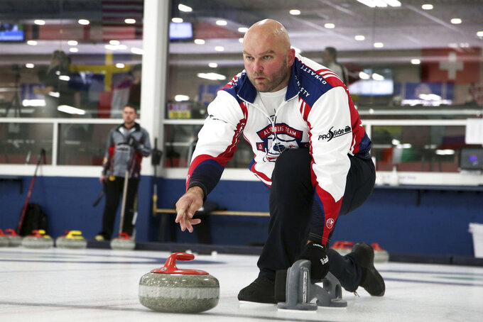 In this Jan. 3, 2019 photo, former NFL offensive lineman Michael Roos practices with his curling team for a competition in Blaine, Minn. Roos and three other former NFL football players who have never curled before will attempt to qualify for the U.S. championships with a goal of making it to the 2022 Olympics. (AP Photo/Jim Mone)