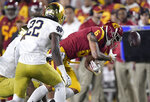 Notre Dame cornerback Troy Pride Jr., left, forces a fumble by Southern California wide receiver Michael Pittman Jr., right, as linebacker Asmar Bilal watches during the first half of an NCAA college football game Saturday, Nov. 24, 2018, in Los Angeles. Notre Dame recovered the ball. (AP Photo/Mark J. Terrill)