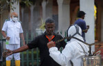 A Sri Lankan municipal health worker disinfects a colleague after the cremation of a COVID-19 victim at a cemetery in Colombo, Sri Lanka, Friday, Jan. 22, 2021. Sri Lanka on Friday approved the Oxford-AstraZeneca vaccine for COVID-19 amid warnings from doctors that front-line health workers should be quickly inoculated to stop the system from collapsing. (AP Photo/Eranga Jayawardena)
