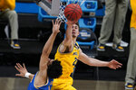 Michigan guard Franz Wagner, right, blocks a shot by UCLA guard Jules Bernard, left, during the first half of an Elite 8 game in the NCAA men's college basketball tournament at Lucas Oil Stadium, Tuesday, March 30, 2021, in Indianapolis. (AP Photo/Michael Conroy)