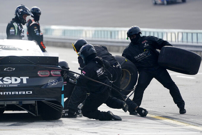 The number 53 car driven by Garrett Smithley gets new tires during a pit stop during a NASCAR Cup Series auto race, Sunday, Feb. 28, 2021, in Homestead, Fla. (AP Photo/Wilfredo Lee)