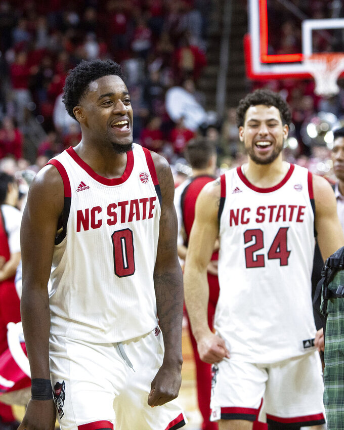 North Carolina State's DJ Funderburk (0) and Devon Daniels (24) leave the court following an NCAA college basketball game against Clemson in Raleigh, N.C., Saturday, Jan. 26, 2019. (AP Photo/Ben McKeown)