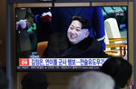 People watch a TV news program reporting about North Korea's test-fire of a