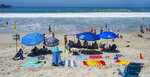 With most of Southern California's coastline is shut down for the Fourth of July holiday due to a spike in coronavirus cases, the beach in San Clemente, Calif., remains open as crowds, socially distanced, fill the sand Saturday, July 4, 2020. (Mark Rightmire/The Orange County Register via AP)