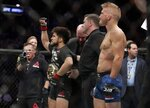 Henry Cejudo, center left, celebrates as TJ Dillashaw reacts after a flyweight mixed martial arts championship bout at UFC Fight Night early Sunday, Jan. 20, 2019, in New York. Cejudo stopped Dillashaw in the first round. (AP Photo/Frank Franklin II)