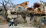 Women stand outside a house damaged by a tornado in the Preston Hollow section of Dallas, Monday, Oct. 21, 2019. (AP Photo/LM Otero)