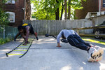 In this Tuesday, May 26, 2020 photo, Damiene Palmer, left, of Fineview and an amateur boxer, and Gerald Sherrell, a pro fighter and season 5 Contender finalist, do pushups while working out and conditioning outside of Sherrell's home in Bellevue, Pa. Since the closing of gym's due to the COVID-19 pandemic, boxers and MMA fighters have taken to the streets and using makeshift home gym's to stay in shape while quarantining. (Michael M. Santiago/Pittsburgh Post-Gazette via AP)