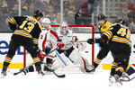 Washington Capitals goaltender Braden Holtby eyes a shot by Boston Bruins' David Krejci (46) as Jake DeBrusk and Charlie Coyle (13) wait in front of the net during the first period of an NHL hockey game Monday, Dec. 23, 2019, in Boston. (AP Photo/Winslow Townson)