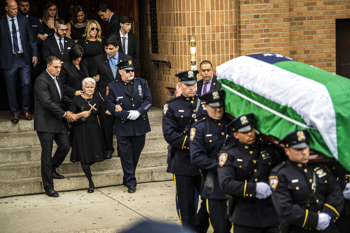 Friends and family of retired New York Police Department Detective Luis Alvarez leave the Immaculate Conception Roman Catholic Church after his funeral services, Wednesday July 3, 2019 in the Queens borough of New York. Alvarez died Saturday, June 29, 2019 after a three-year battle with colorectal cancer. He attributed his illness to the three months he spent digging through rubble at the World Trade Center's twin towers after the 2001 terrorist attacks. (Alejandra Villa Loarca/Newsday via AP)