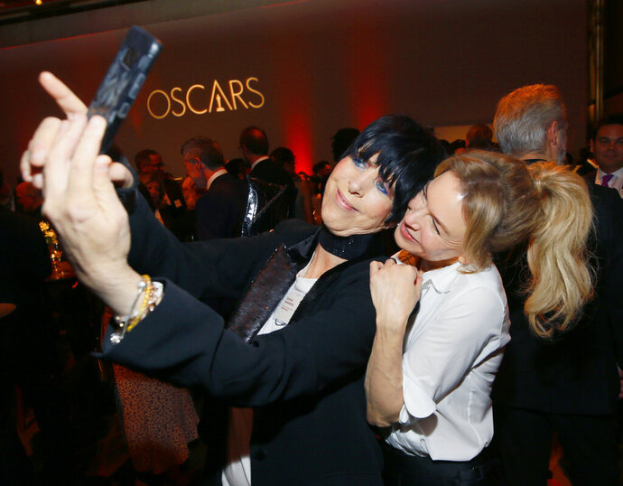 Diane Warren, left, and Renee Zellweger take a selfie at the 92nd Academy Awards Nominees Luncheon at the Loews Hotel on Monday, Jan. 27, 2020, in Los Angeles. (Photo by Danny Moloshok/Invision/AP)