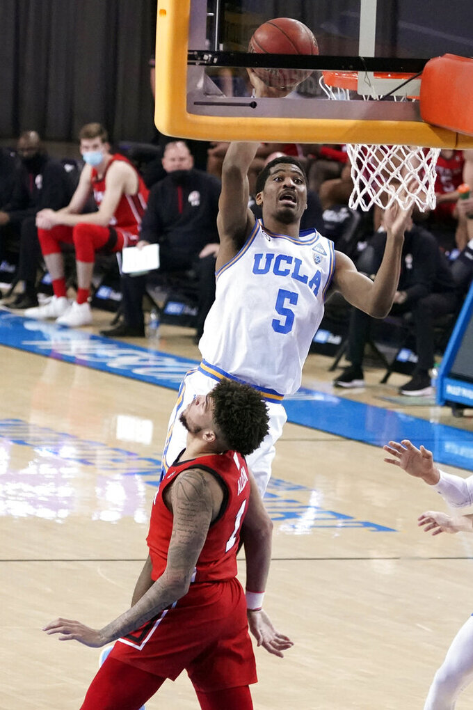 UCLA guard Chris Smith (5) shoots over Utah forward Timmy Allen during the second half of an NCAA college basketball game Thursday, Dec. 31, 2020, in Los Angeles. (AP Photo/Marcio Jose Sanchez)