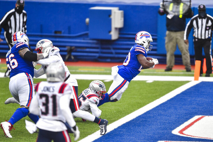 Buffalo Bills' Zack Moss, right, dives past New England Patriots' Terrence Brooks to score a touchdown during the first half of an NFL football game Sunday, Nov. 1, 2020, in Orchard Park, N.Y. (AP Photo/Adrian Kraus)