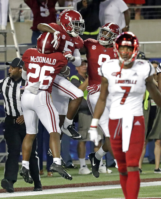 Alabama defensive back Shyheim Carter (5) celebrates with defensive back Kyriq McDonald (26) and linebacker Eyabi Anoma (9) after intercepting a pass for a 45-yard return for a touchdown, as Louisville wide receiver Dez Fitzpatrick (7) walks off the field during the second half of an NCAA college football game, Saturday, Sept. 1, 2018, in Orlando, Fla. (AP Photo/John Raoux)