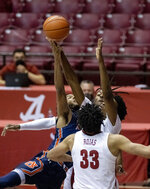 Auburn guard Jamal Johnson, left, shoots as Alabama forward James Rojas (33), forward/guard Herbert Jones (1) and guard John Petty Jr., from front, close in during the first half of an NCAA college basketball game Tuesday, March 2, 2021, in Tuscaloosa, Ala. (AP Photo/Vasha Hunt)