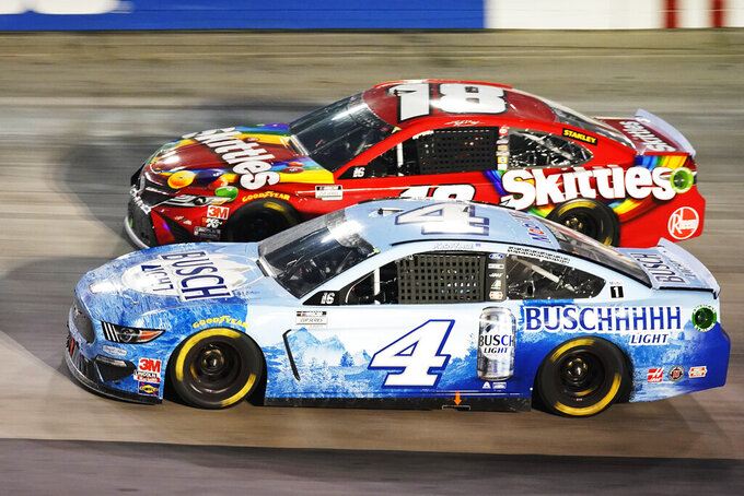 Kevin Harvick (4) passes Kyle Busch (18) during the NASCAR Cup Series auto race Saturday, Sept. 19, 2020, in Bristol, Tenn. (AP Photo/Steve Helber)
