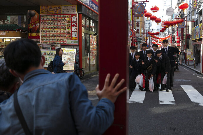 In this Feb. 13, 2020, photo, a group of students gather for a group picture in Yokohama's Chinatown, near Tokyo. A top Olympic official made clear Friday the 2020 Games in Tokyo will not be cancelled despite the virus that has spread from China. (AP Photo/Jae C. Hong)