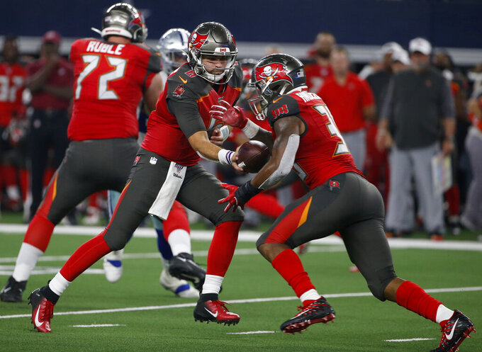 Tampa Bay Buccaneers quarterback Vincent Testaverde, left, lands the ball off to running back Bruce Anderson III, right, in the second half of a preseason NFL football game against the Dallas Cowboys in Arlington, Texas, Thursday, Aug. 29, 2019. (AP Photo/Ron Jenkins)