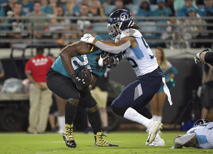 Tennessee Titans linebacker Sharif Finch (56) stops Jacksonville Jaguars running back Leonard Fournette (27) on a run during the first half of an NFL football game Thursday, Sept. 19, 2019, in Jacksonville, Fla. (AP Photo/Phelan Ebenhack)