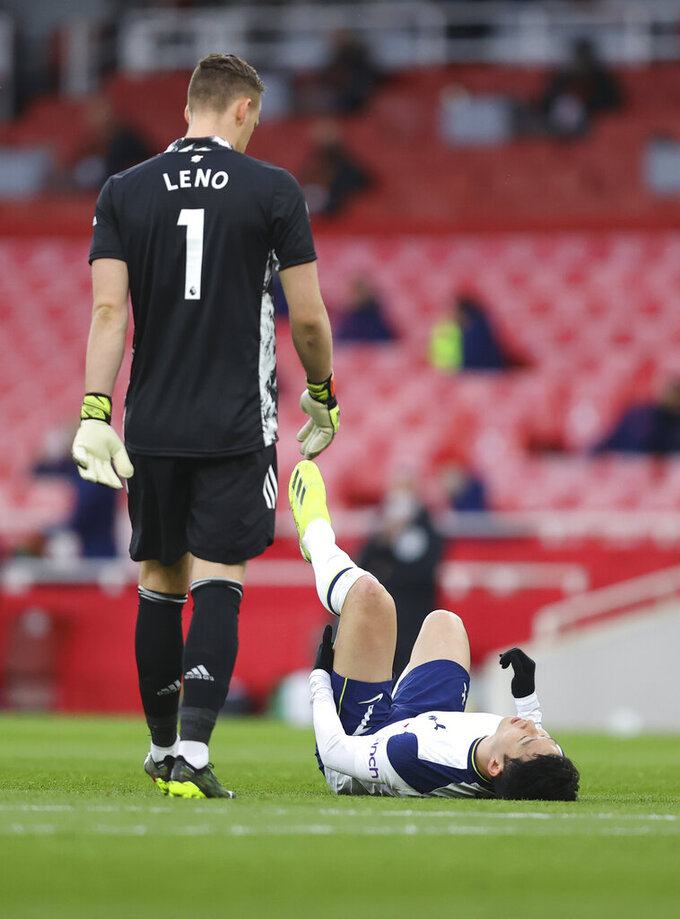 Tottenham's Son Heung-min lies on the pitch in pain during the English Premier League soccer match between Arsenal and Tottenham Hotspur at the Emirates stadium in London, England, Sunday, March 14, 2021. (Julian Finney/Pool via AP)