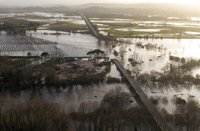 A road is flooded by the river Ter in Verges, Girona, Spain, Thursday, Jan. 23, 2020. A calamitous storm has killed at least 11 people in Spain and left five others missing, as well as causing rivers to overflow their banks and contaminating vast agricultural areas in eastern Spain with salty seawater. (AP Photo/Emilio Morenatti)